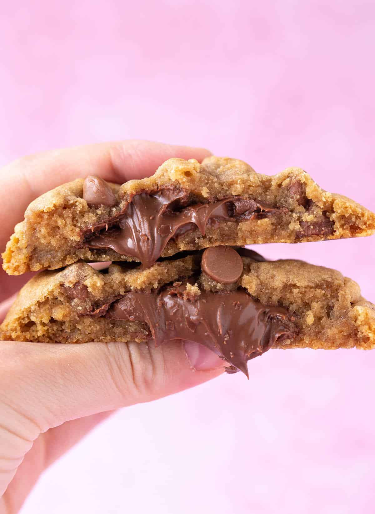 A hand holding a Nutella Stuffed Cookie with gooey Nutella spilling out