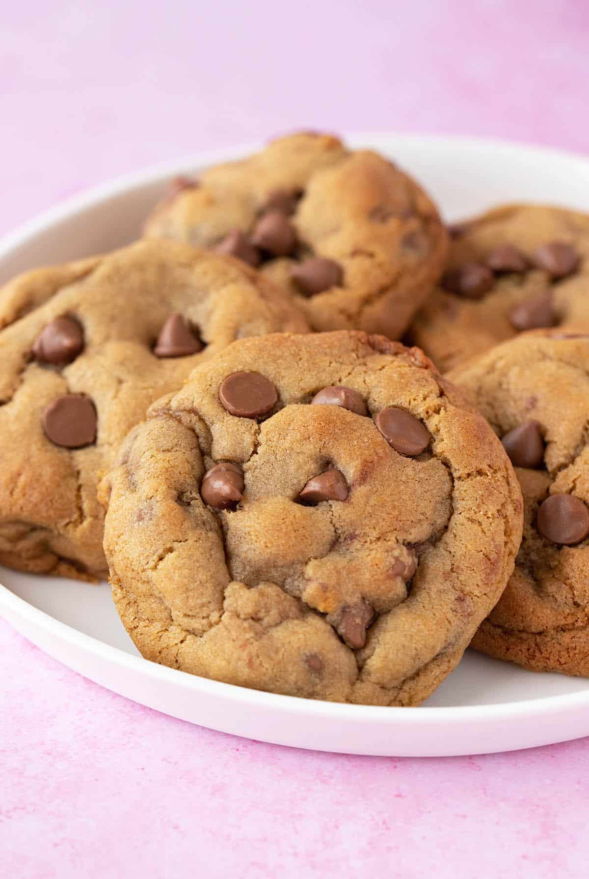 A plate of Chocolate Chip Cookies on a pink background