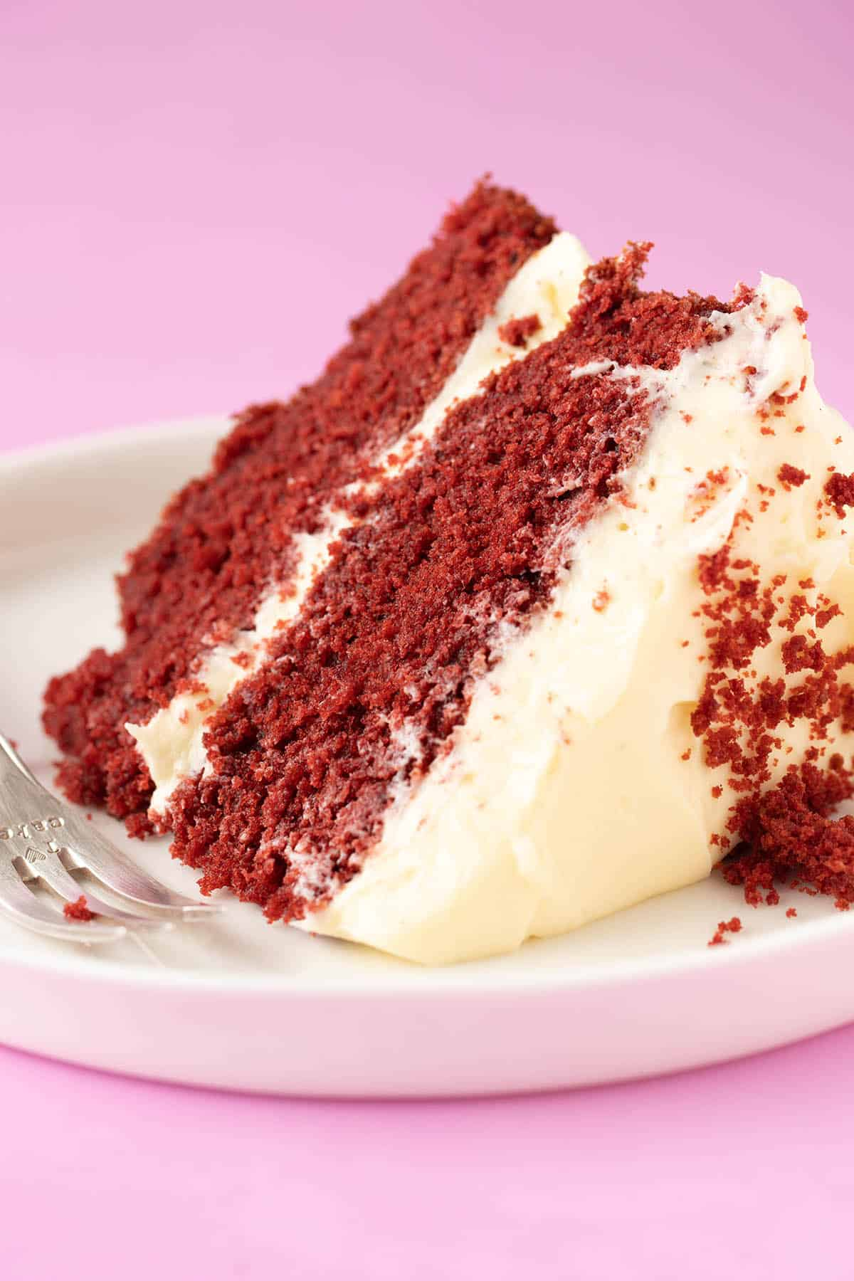 A beautiful slice of Red Velvet Cake on a pink background.