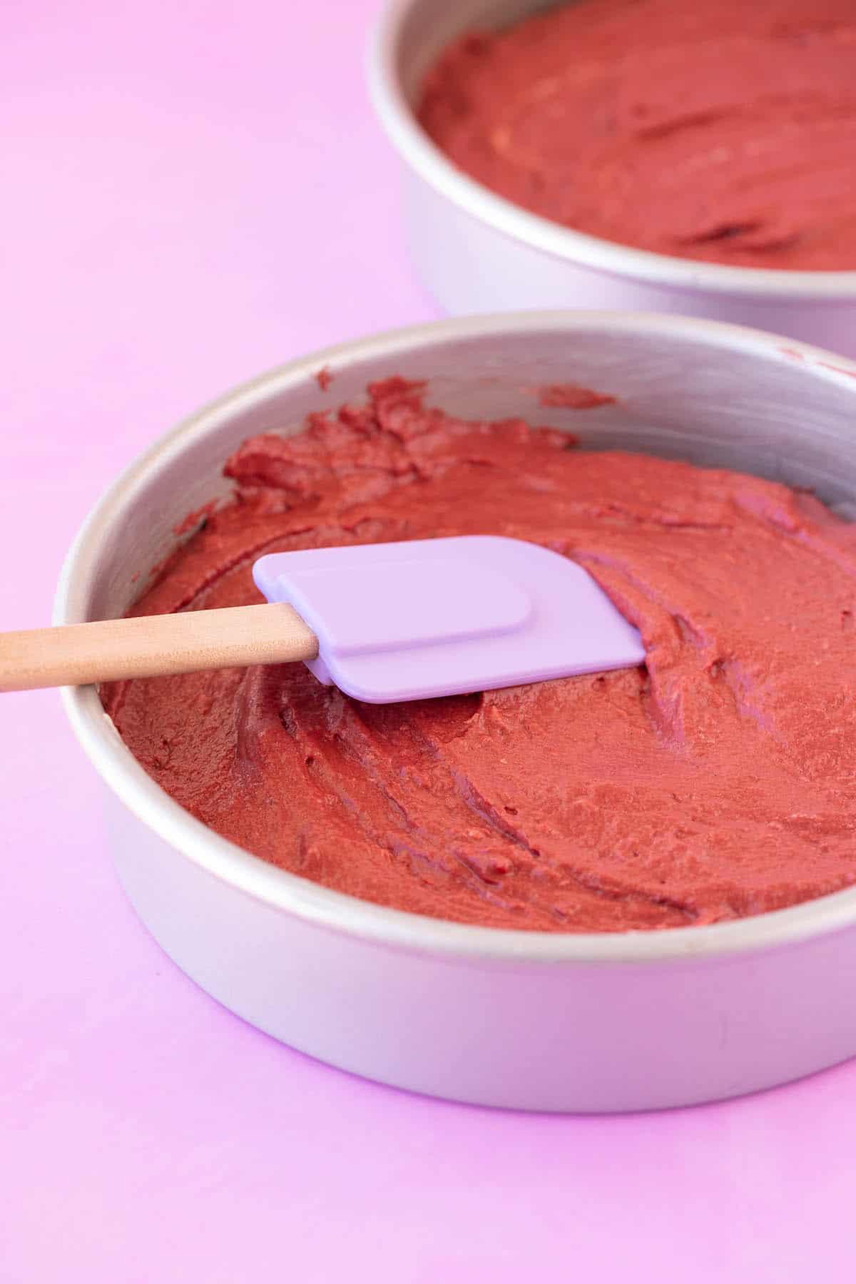 Cake pans filled with red velvet cake batter