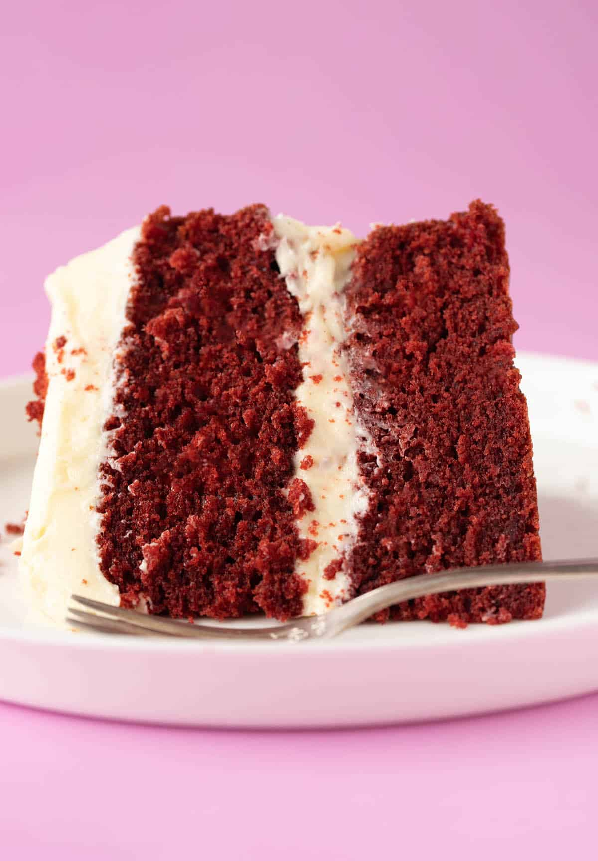 A close up of a slice of Red Velvet Cake on a white plate