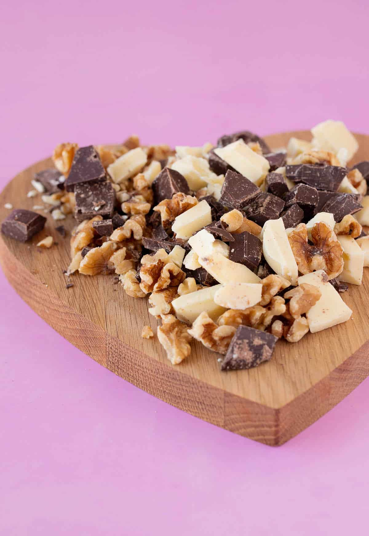 A chopping board with chunks of chocolate on it
