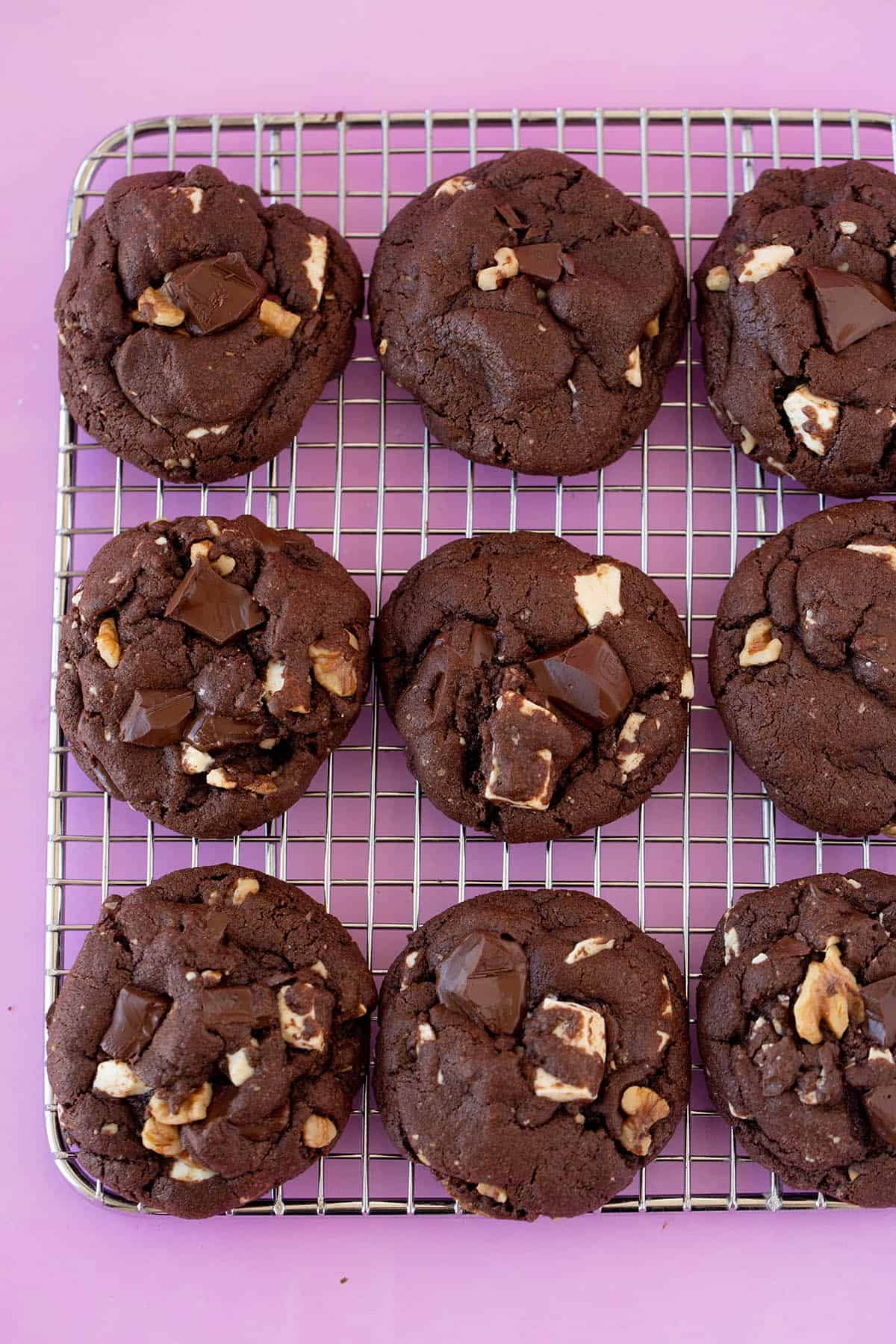 Chunky walnut chocolate cookies on a pink background.