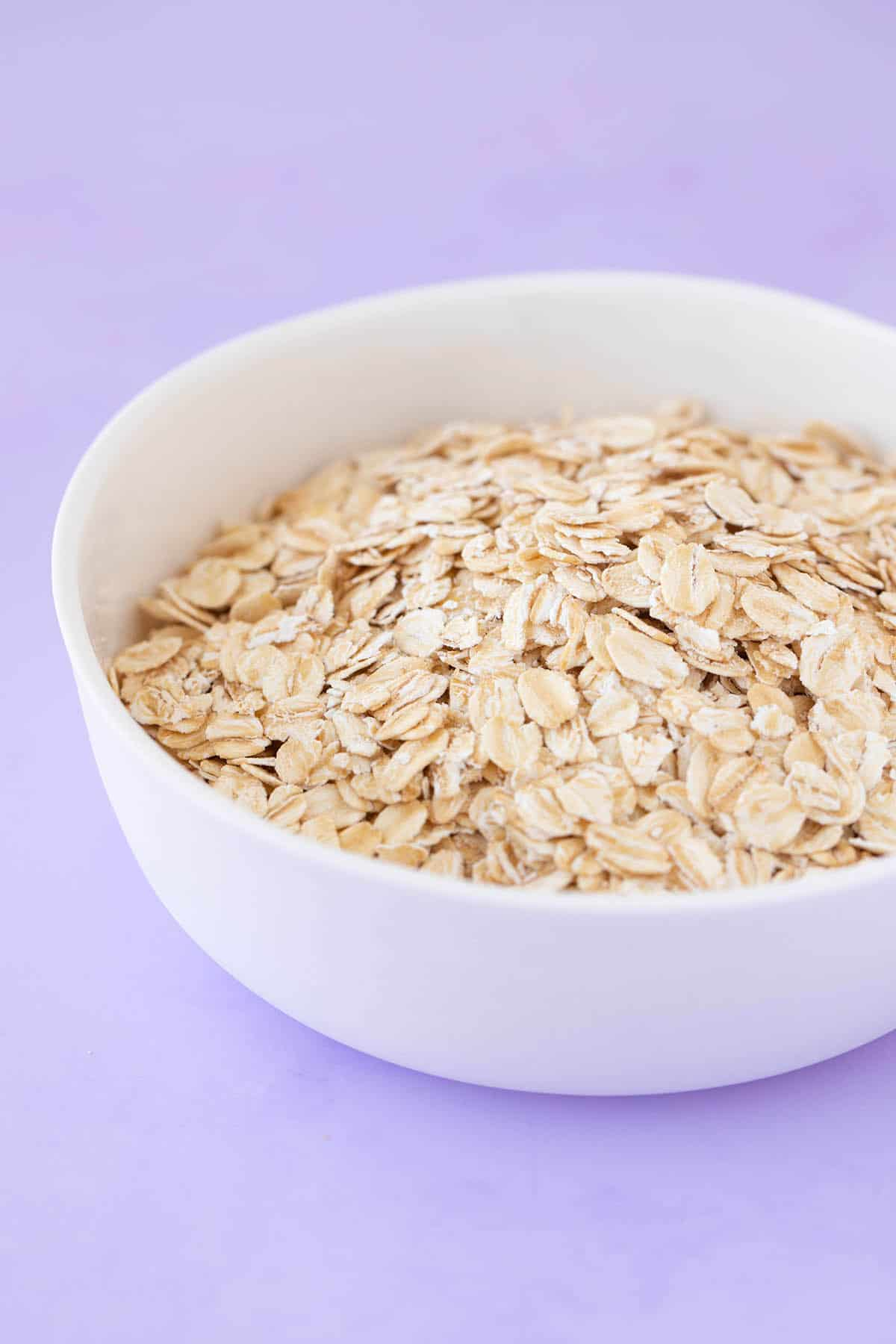 A white bowl filled with whole rolled oats