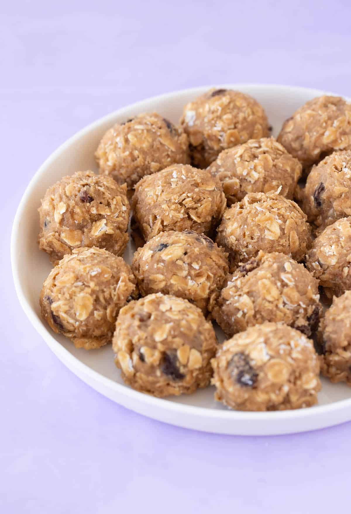 A white plate with balls of Oatmeal Raisin cookie dough