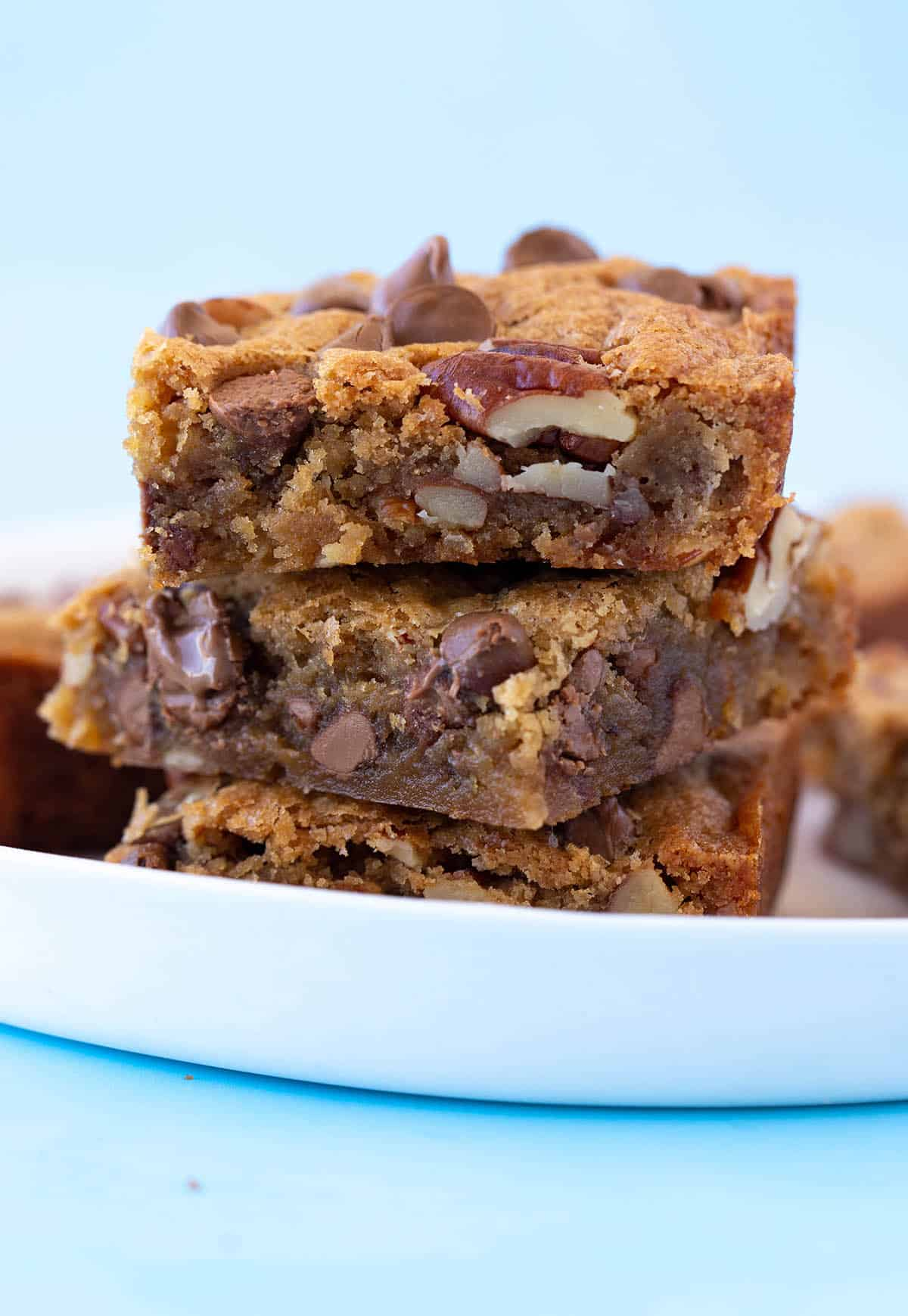 A tall stack of Pecan Chocolate Chip Blondies on a blue background.