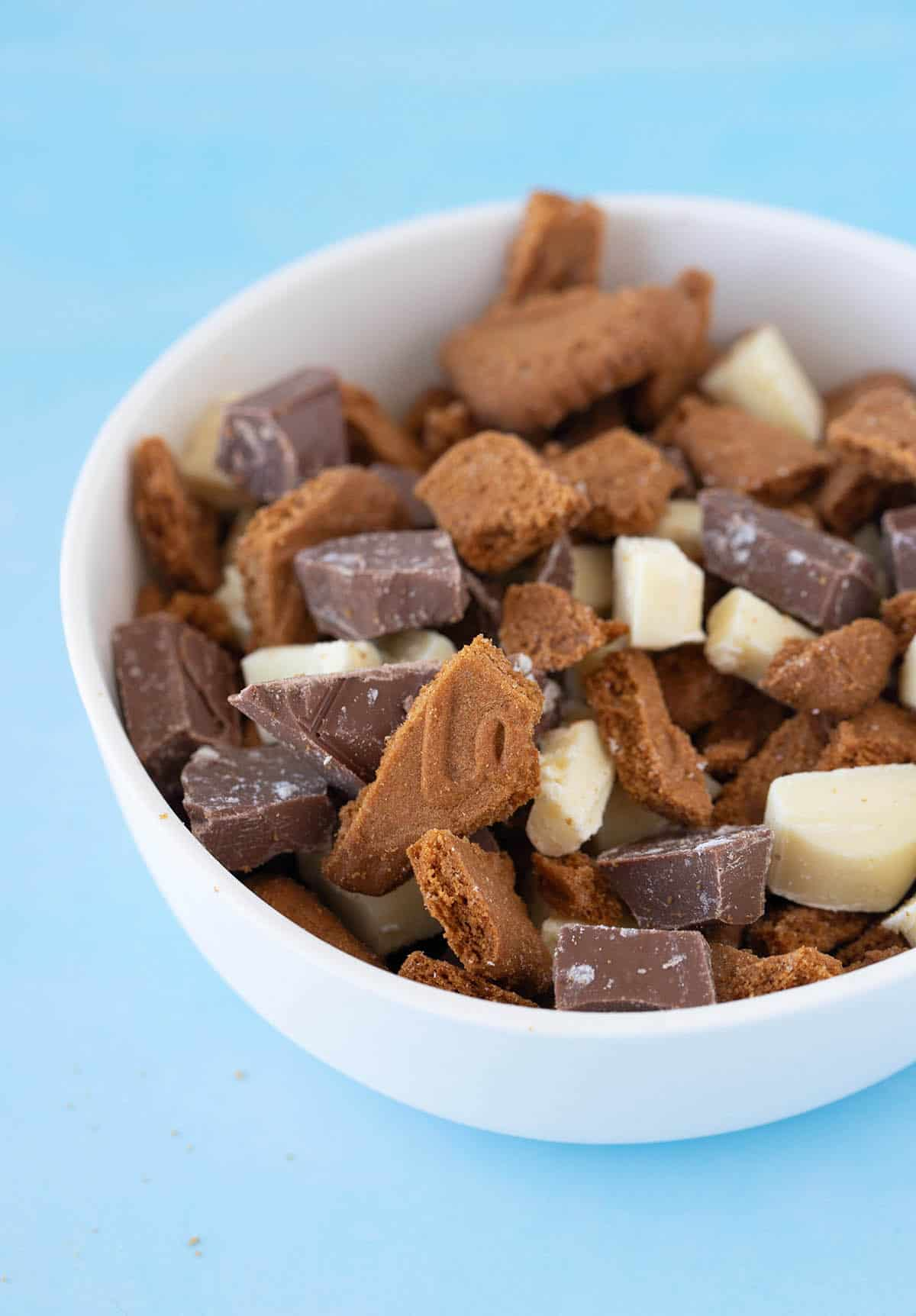 A white bowl filled with chunks of chocolate and Lotus cookies.