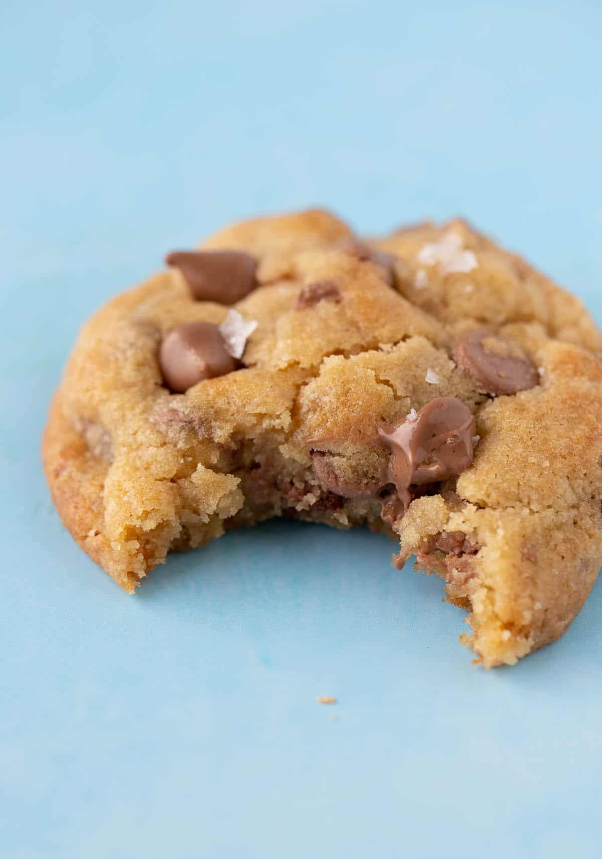 Close up of a chocolate chip cookie with a bite taken out of it