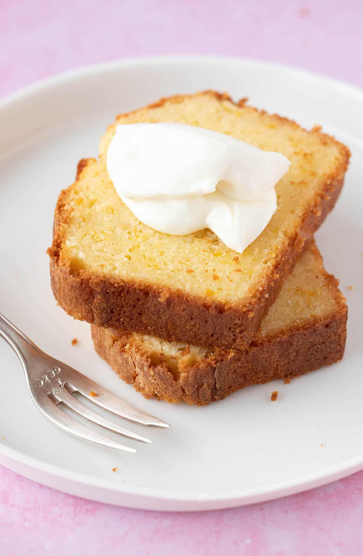 A piece of orange cake topping with whipped cream