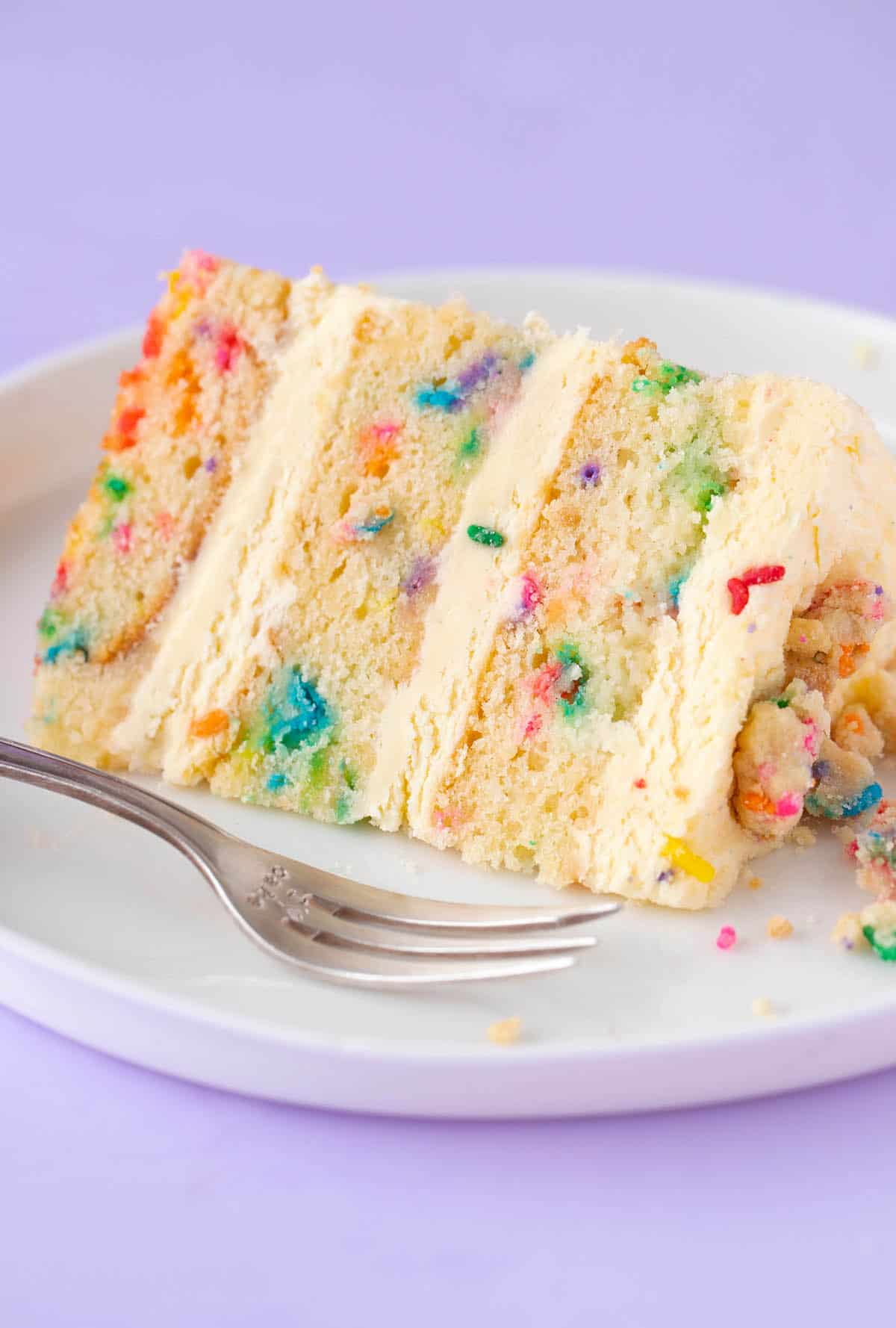 A slice of homemade Funfetti Birthday Cake on a white plate