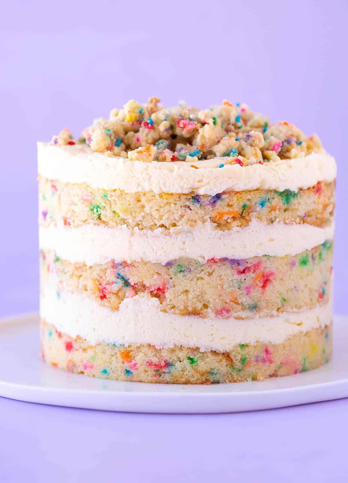 A beautiful homemade Milk Bar Birthday Cake on a purple background.