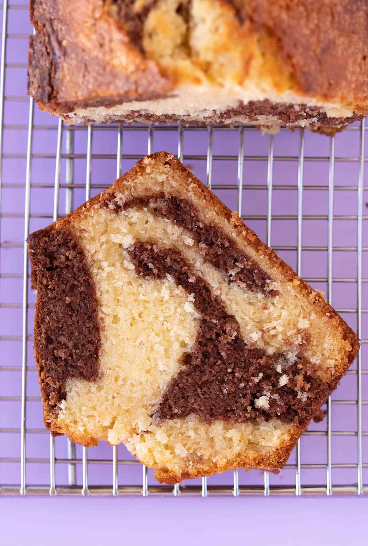 Top view of a piece of homemade Marble Cake on a purple background.