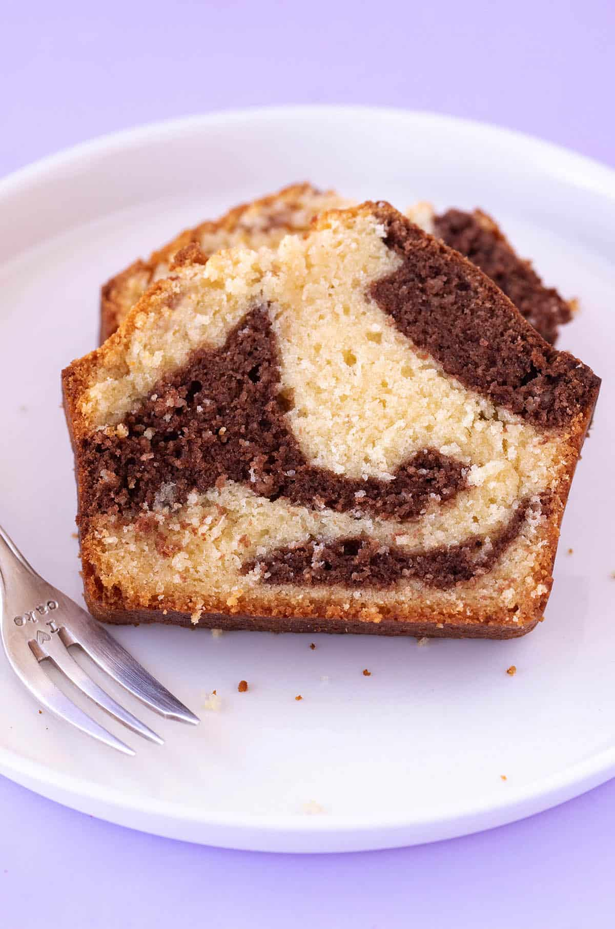 Close up of a slice of homemade Marble Cake on a white plate with a decorative fork.