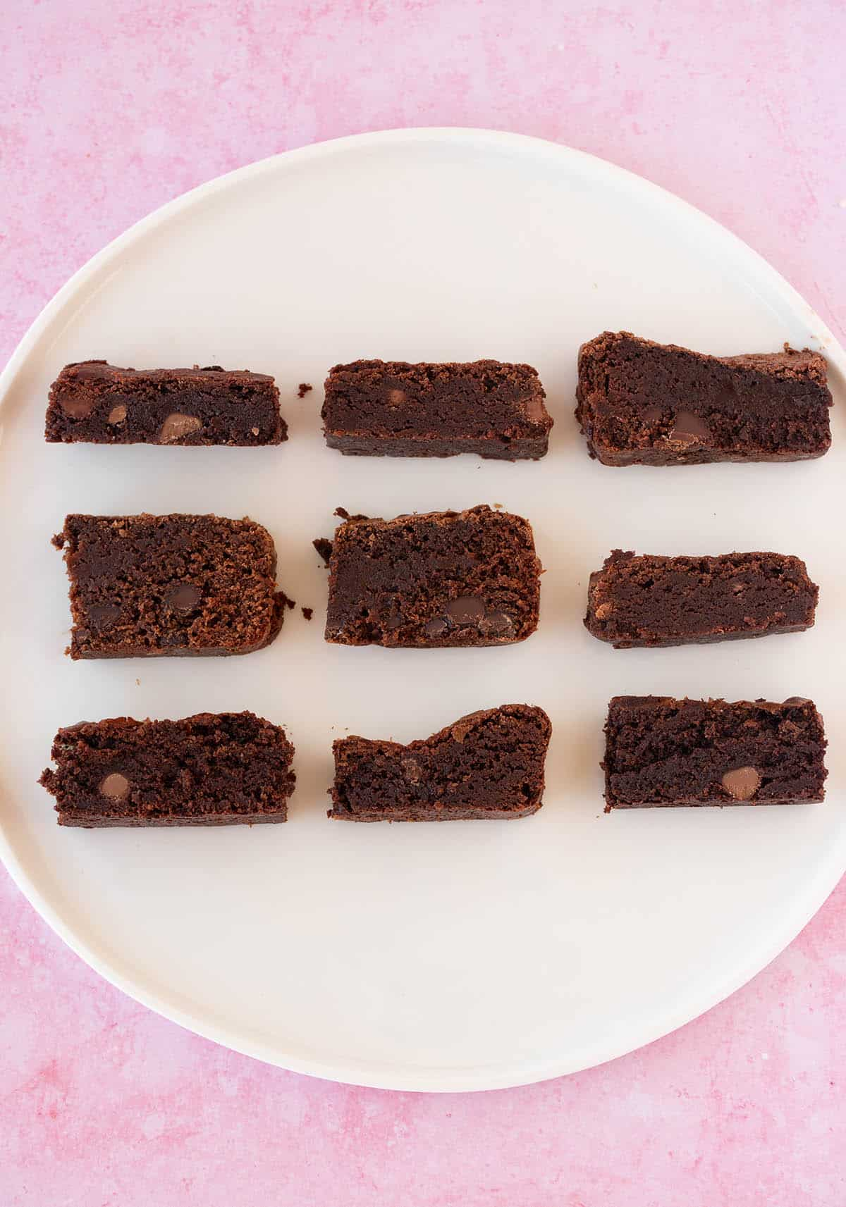 9 different brownies on a pink background.
