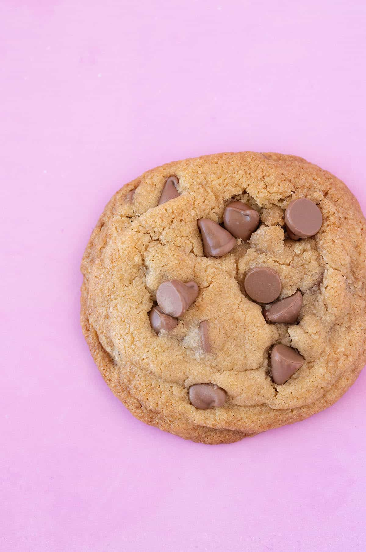 Top view of a golden chocolate chip cookie on a pink background