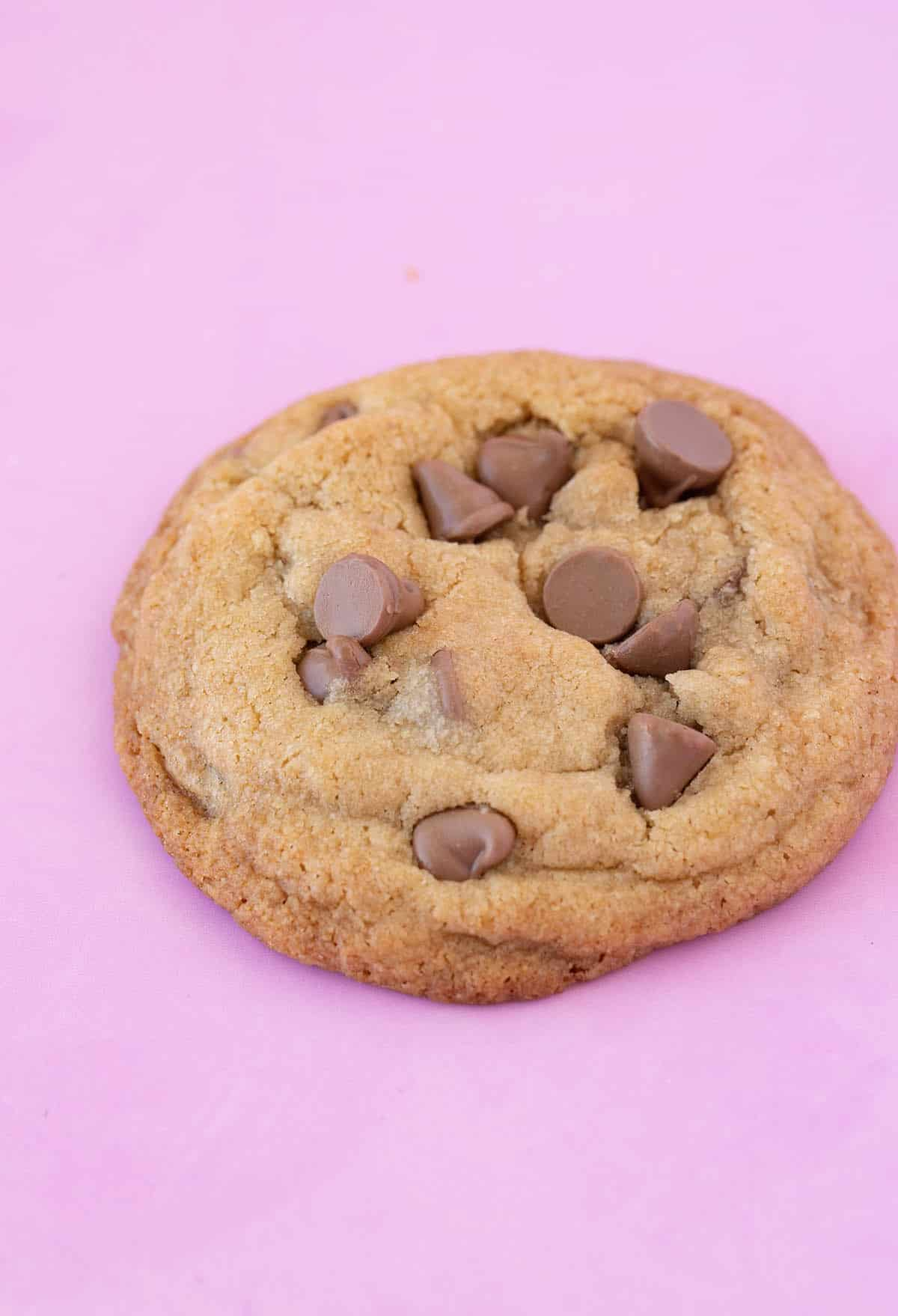 Perfect chocolate chip cookie on a pink background with a bite taken out of it