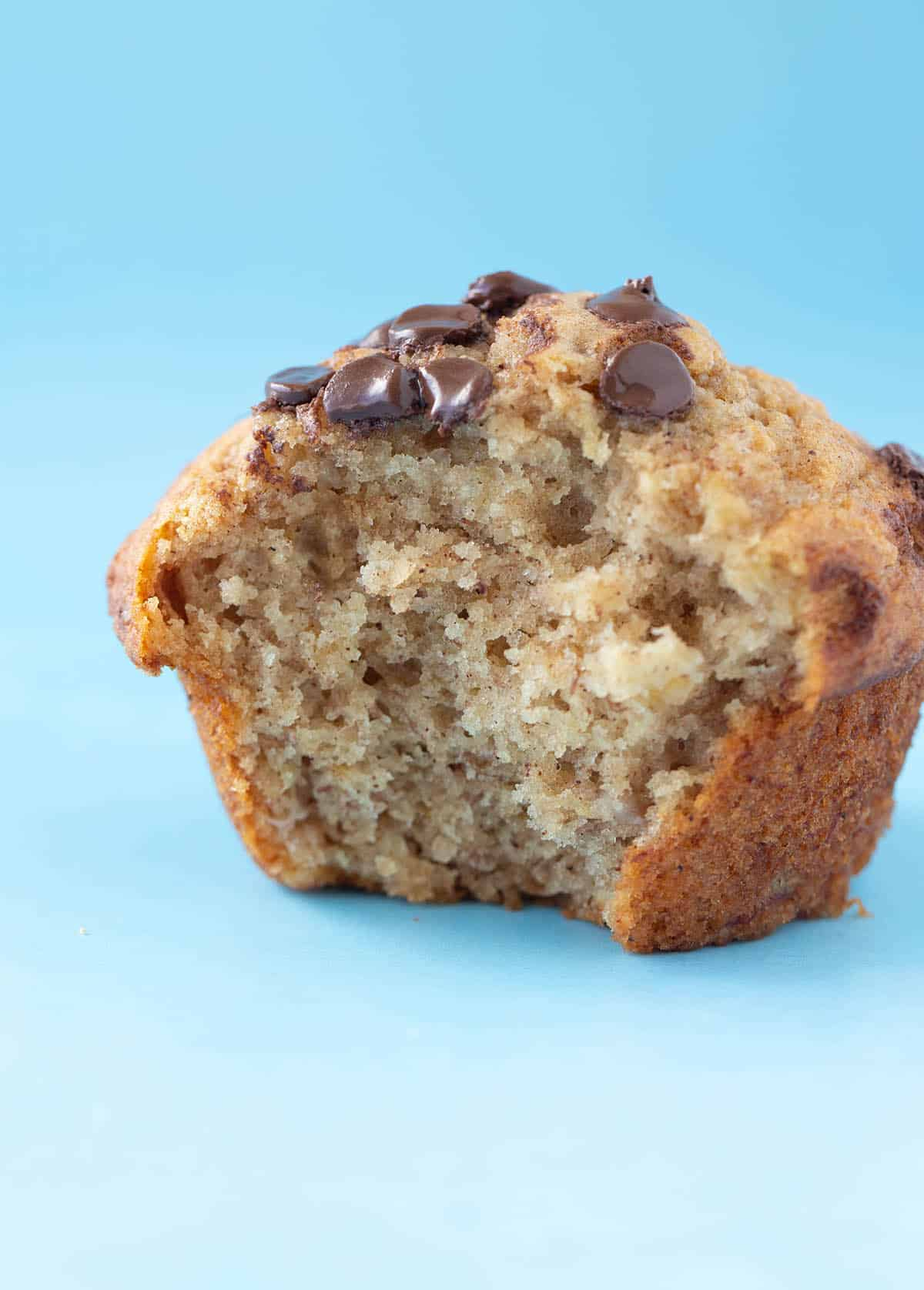 Close up of a homemade banana muffin with a bite taken out of it.