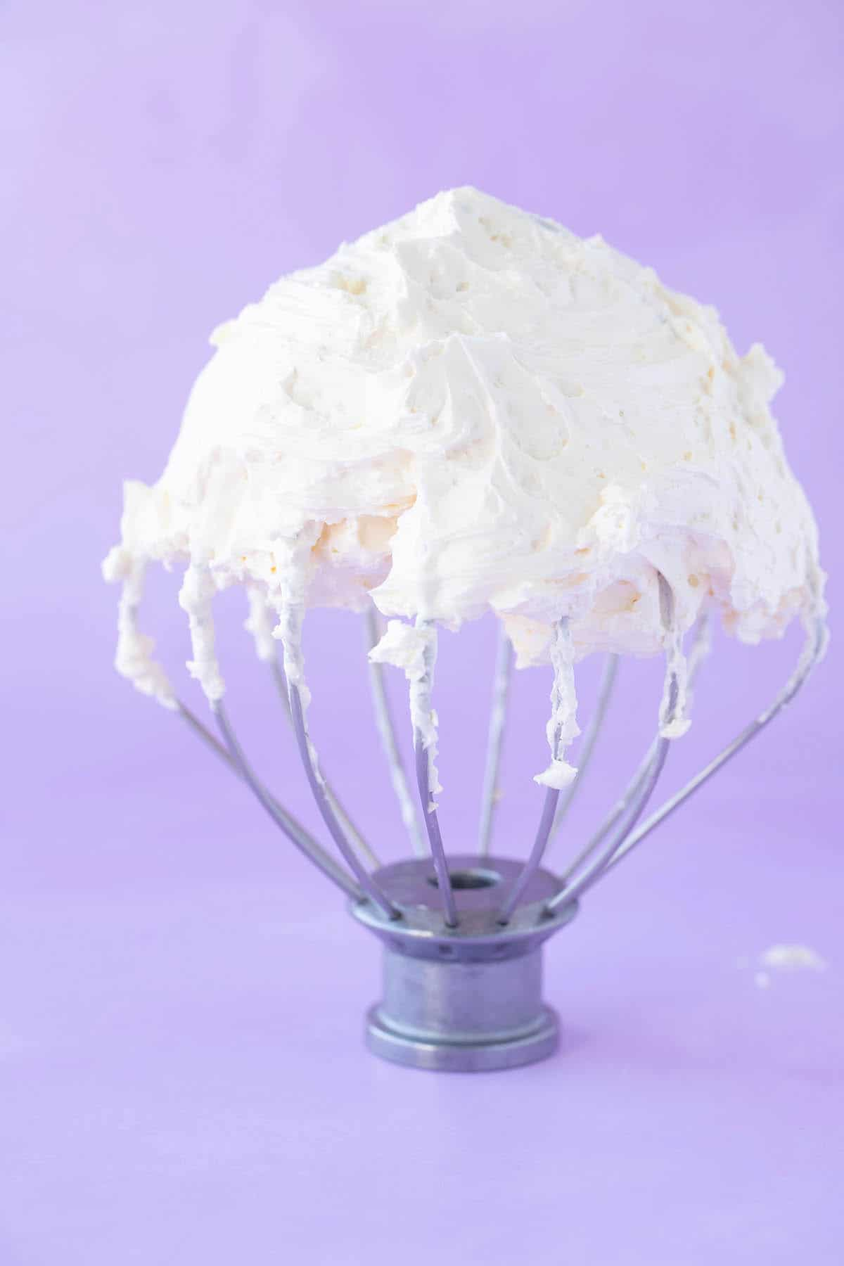 A whisk covered in creamy Swiss Meringue Buttercream.