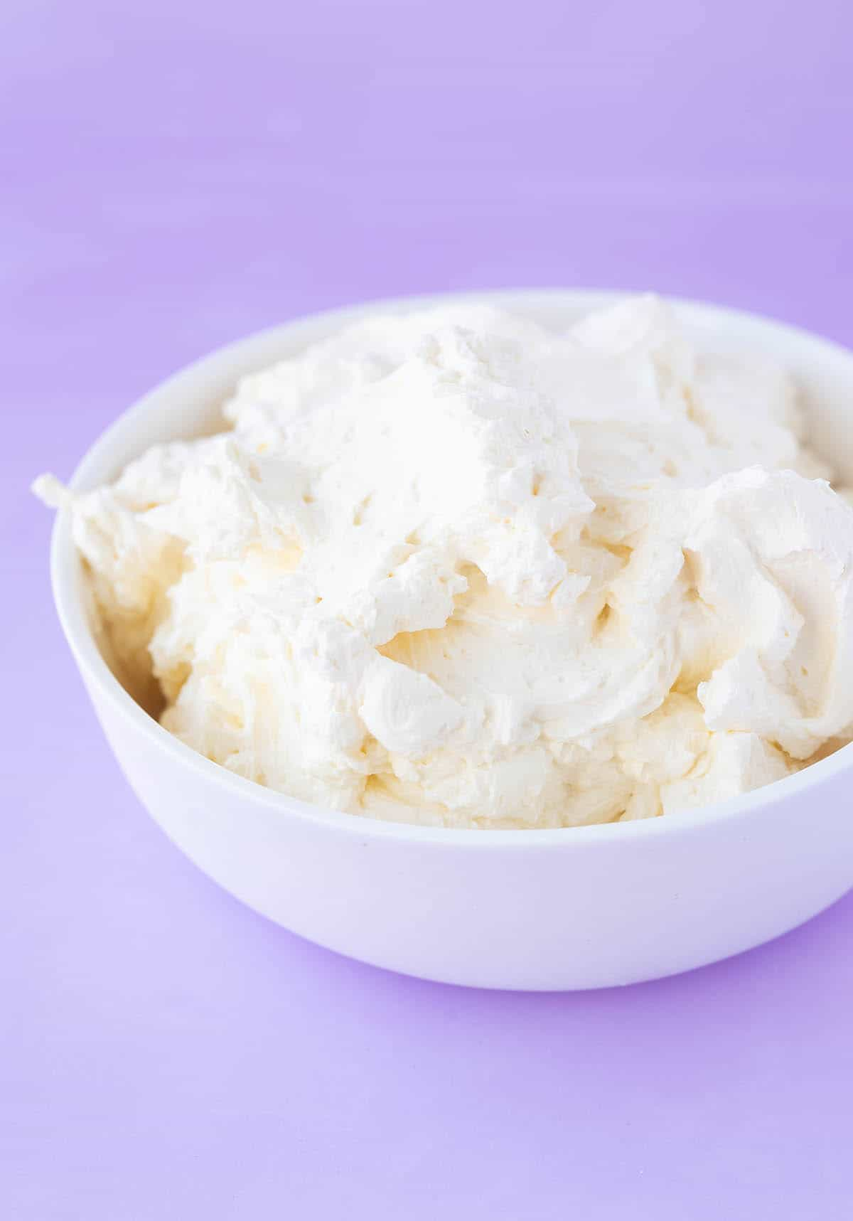 A white bowl filled with creamy Swiss Meringue Buttercream.